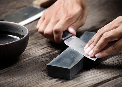 Hands Holding Knife Against Whetstone